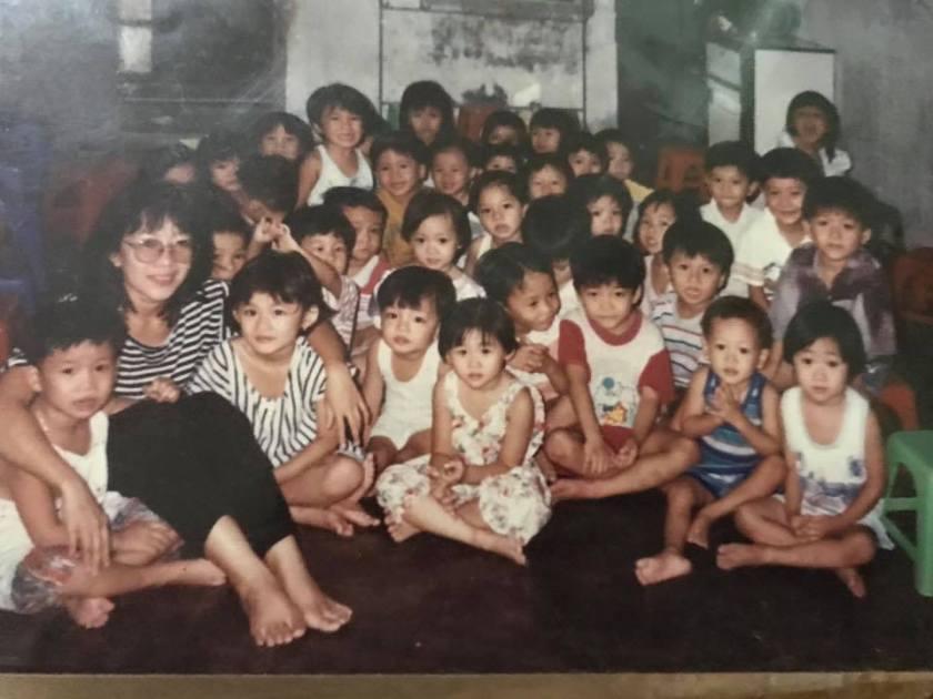 Cô giáo Thái Lai, thứ hai bên trái sang, áo sọc đen trắng, quần đen
